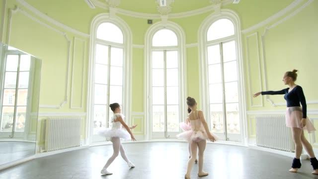 female ballet dancer leads three young ballerinas, sweeping across the studio floor - バレリーナ点の映像素材/bロール