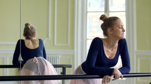 female ballet dancer leans over the ballet barre and stares whistfully out of the window - barre stock videos & royalty-free footage