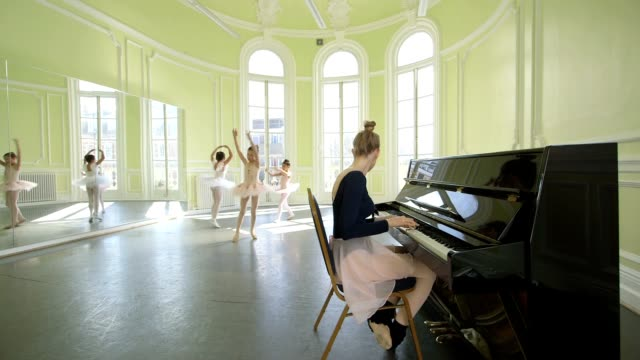 vídeos y material grabado en eventos de stock de female ballet dancer plays the piano in the foregound whilst instructing three young ballerinas on their movements as they twirl and glide through the studio in the background - malla de gimnasia
