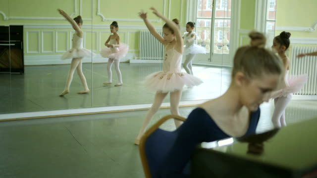 female ballet dancer plays the piano in the foregound whilst instructing three young ballerinas on their movements as they twirl and glide through the studio in the background - gymnastikanzug stock-videos und b-roll-filmmaterial