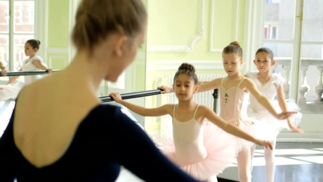female ballet dancer stands before a trio of young ballerinas demonstrating the movements and encouraging leg and arm extension - tiptoe stock videos & royalty-free footage