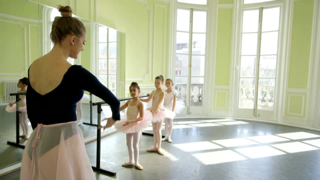 vidéos et rushes de female ballet dancer stands before a trio of young ballerinas demonstrating the movements and encouraging leg and arm extension - barre de danse