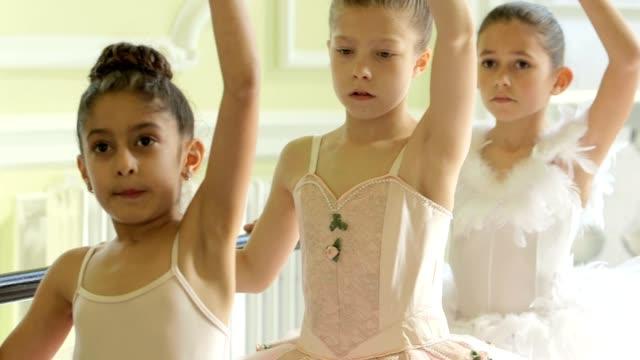 vídeos y material grabado en eventos de stock de female ballet dancer stands before a trio of young ballerinas demonstrating the movements and encouraging leg and arm extension - barra de deportes