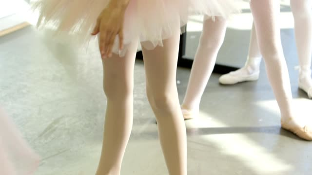 female ballet dancer stands before a trio of young ballerinas demonstrating the movements and encouraging leg and arm extension - unschuld stock-videos und b-roll-filmmaterial