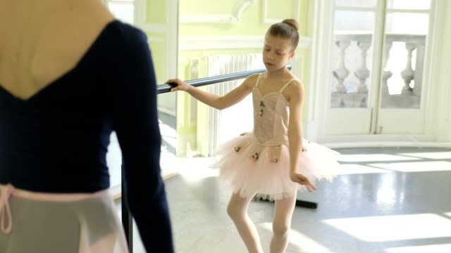 female ballet dancer stands before a young ballerina demonstrating the movements and encouraging leg and arm extension with the mirror - ballettstange stock-videos und b-roll-filmmaterial