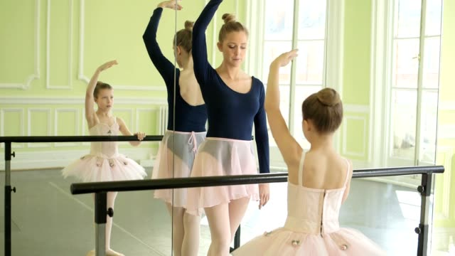 vidéos et rushes de female ballet dancer stands before a young ballerina demonstrating the movements and encouraging leg and arm extension with the mirror - barre de danse