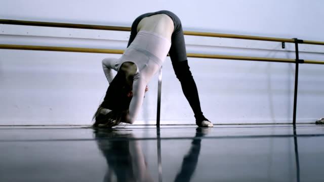 ws female ballet dancer stretching /  los angles, california, usa  - バレエ練習用バー点の映像素材/bロール