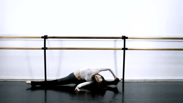 vidéos et rushes de ws female ballet dancer stretching on floor /  los angles, california, usa  - barre de danse