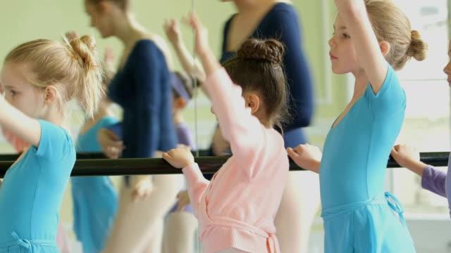 vídeos y material grabado en eventos de stock de female ballet dancer strides along the barre in the backgound encouraging the four young ballerinas as they practice their movements - barra de deportes