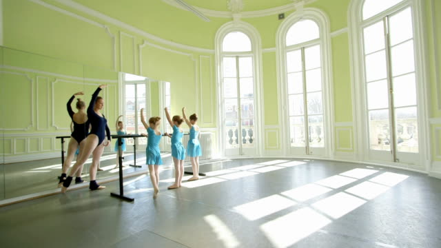 female ballet dancer strides along the barre in the backgound encouraging the three young ballerinas as they practice their movements - barre stock videos & royalty-free footage