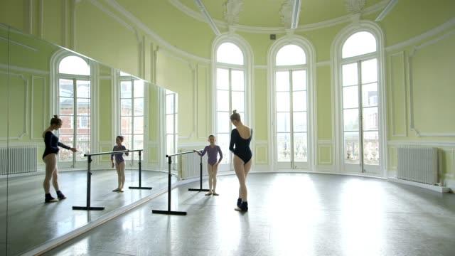 vídeos y material grabado en eventos de stock de mls female ballet dancer supervises a younger ballerina and teaches her movements - barra de deportes