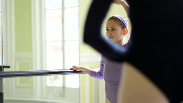 vídeos y material grabado en eventos de stock de ms female ballet dancer supervises a younger ballerina and teaches her movements - barra de deportes