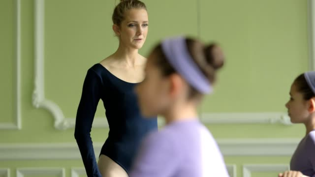 ms female ballet dancer supervises a younger ballerina and teaches her movements - kosmetisches stirnband stock-videos und b-roll-filmmaterial