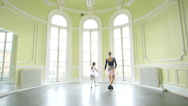 female ballet dancer supervises young ballerina on movements gliding across the dancefloor - ballet shoe stock videos and b-roll footage