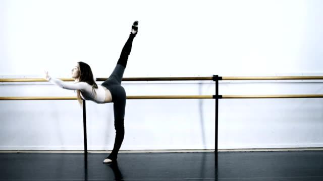 WS Female ballet dancer warming up on bar /  Los Angles, California, USA