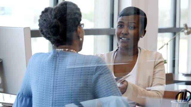 Vrouw Bank medewerker reviews Bank informatieve flyer met klant