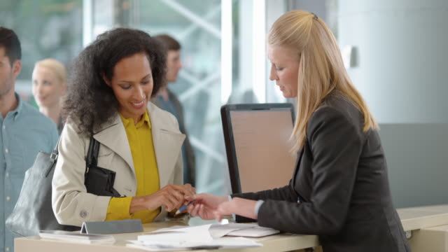 female bank teller advising a female customer before she signs a document - signature stock videos and b-roll footage