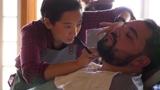 CU ZI R/F Female barber focused on shaving mans beard with straight razor