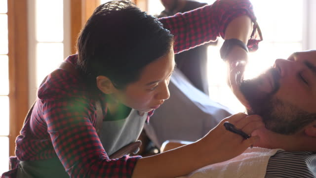 CU TD Female barber shaving client with straight razor in barber shop