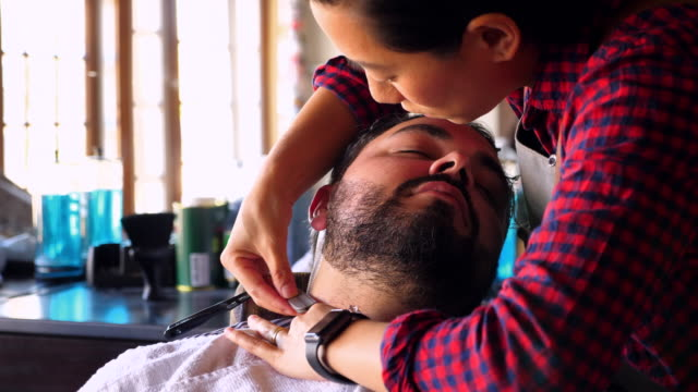 CU TS Female barber shaving client with straight razor