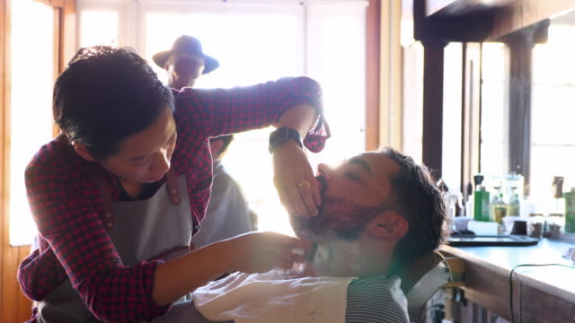 ms pan female barber shop owner applying shaving cream with brush to client seated in barbers chair - gingham stock videos & royalty-free footage