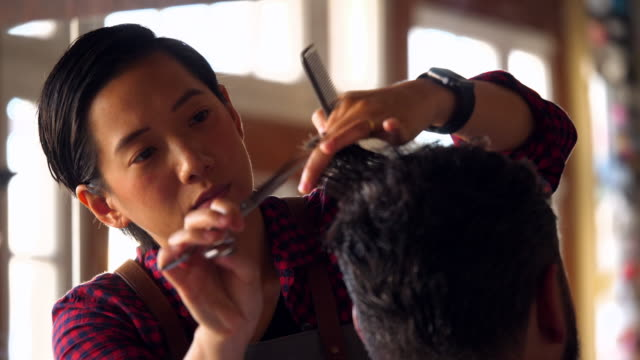 cu r/f female barber shop owner using comb and scissors to cut mans hair - barber stock videos & royalty-free footage