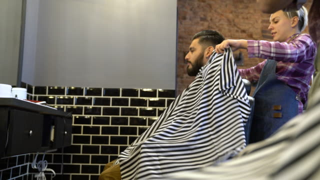 female barber spreading cape on customer in salon - adjusting stock videos & royalty-free footage