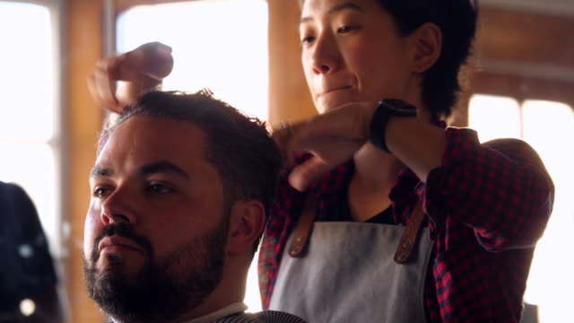 cu r/f female barber styling clients hair in barber shop - barber stock videos & royalty-free footage