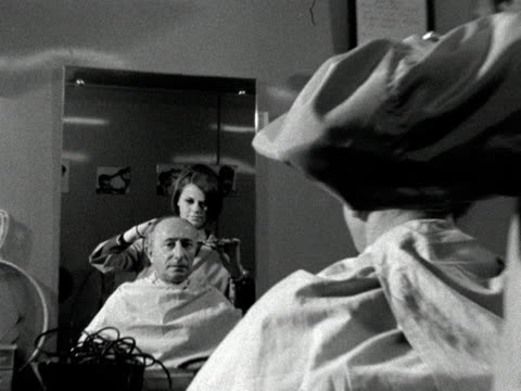 A female barber trims the hair of a customer