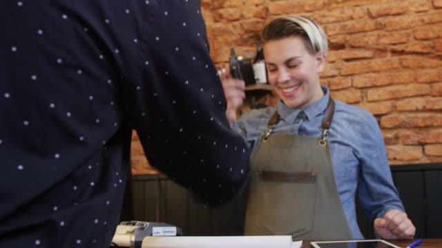 vídeos de stock, filmes e b-roll de feminino barbeiro usando o leitor de cartão de crédito no balcão - recebendo
