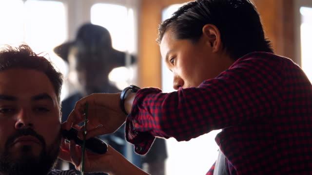 cu r/f female barber using trimmer to style mans hair - 30 34 ��r bildbanksvideor och videomaterial från bakom kulisserna