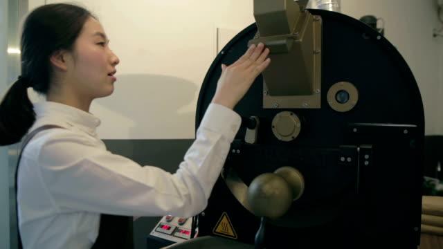 Female Barista handling coffee machine and checking temperature