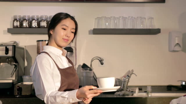 Female Barista holding coffee cup in her hands in cafe