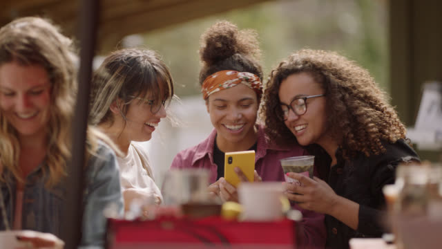 a female barista laughs at a phone together with customers at a mobile coffee truck - booth stock videos & royalty-free footage