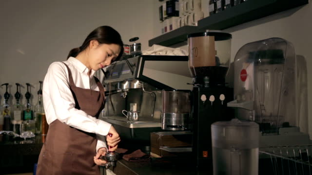 Female barista making coffee with machine