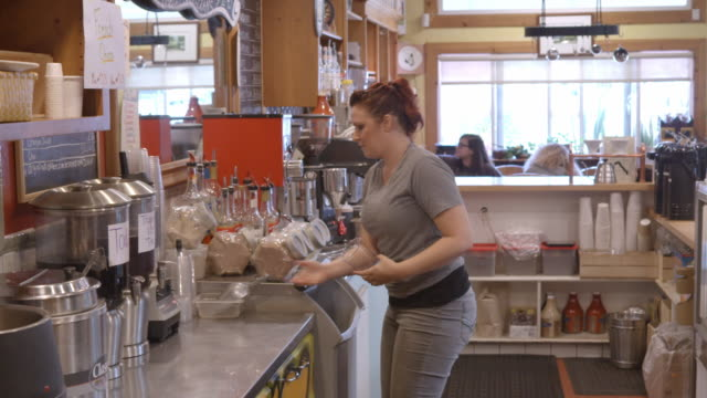 DS of female barista preparing iced drink and cashier working at cash register behind counter of coffee house / Redlands, California, USA