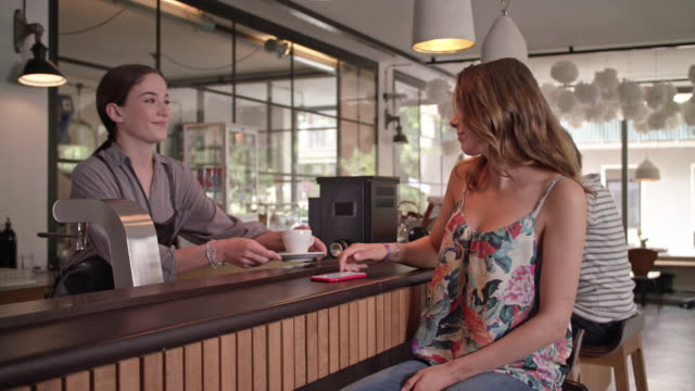 female barista serves coffee to a young, beautiful woman waiting for a date while she is using her smartphone