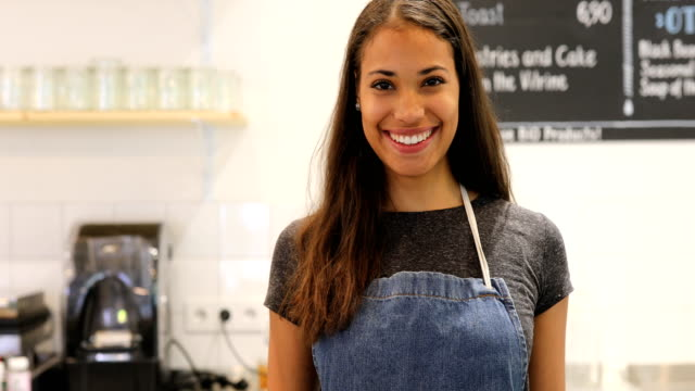female barista smiling at counter in cafe - apron stock videos & royalty-free footage