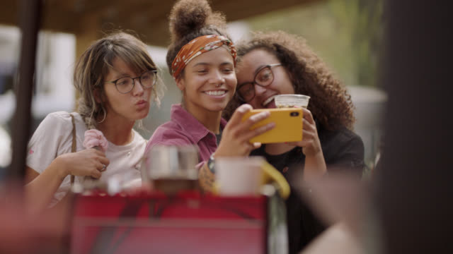 vidéos et rushes de a female barista takes a selfie with her customers at a mobile coffee truck - vie réelle