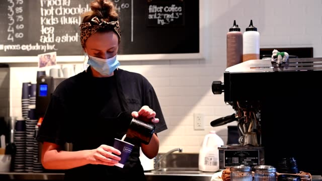 female barista wearing a protective face mask - bakery stock videos & royalty-free footage