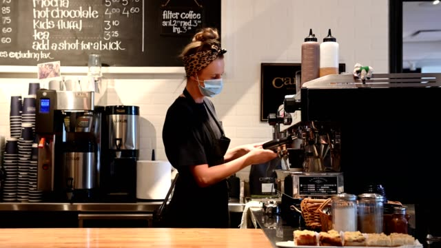 female barista wearing a protective face mask - place of work stock videos & royalty-free footage