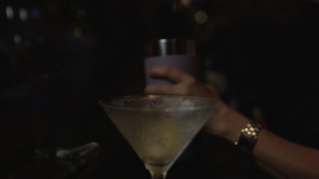stockvideo's en b-roll-footage met a female bartender pours vodka into a shaker with a frosted martini glass waiting. - martiniglas