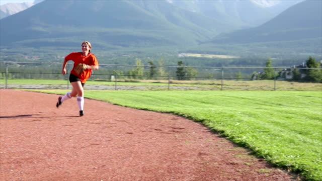 Female baseball player catches softball, mountain field