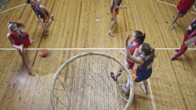Female basketball player performing point shoot during training match