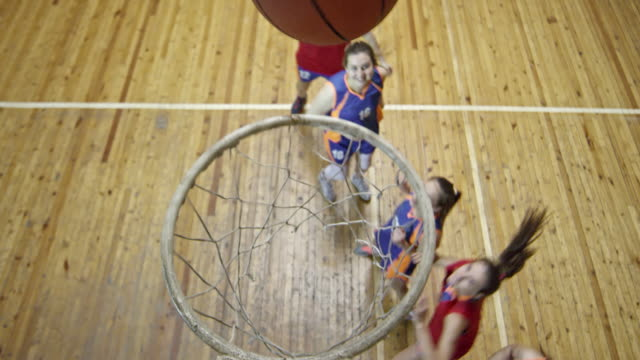 Female basketball player shooting ball into net