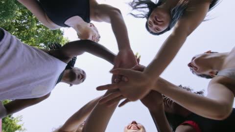 vidéos et rushes de joueurs féminins de basket-ball empilant des mains contre le ciel - vue en contre plongée verticale