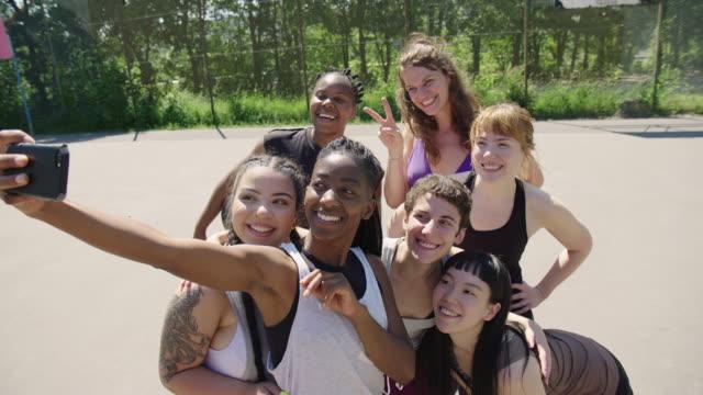 vídeos de stock, filmes e b-roll de jogadores de basquetebol fêmeas que tomam o selfie na corte - amizade feminina