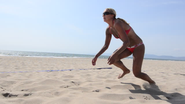 DS WS TS A female beach volleyball player diving for the ball.