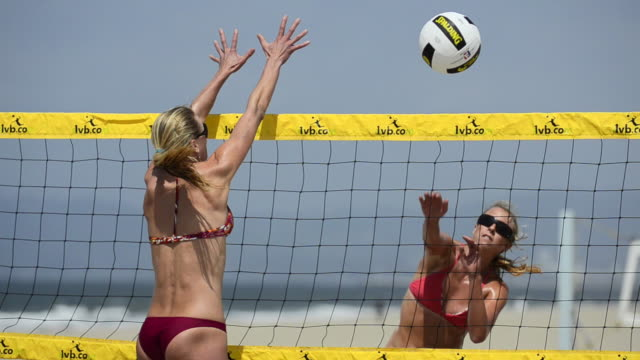 cu of female beach volleyball players spiking and blocking at the net. - volleyball net stock videos & royalty-free footage