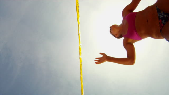 pov la ws of female beach volleyball players spiking and blocking at the net with sun. - 網状点の映像素材/bロール